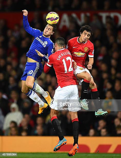Eden Hazard of Chelsea goes up for a header with Rafael and Chris Smalling of Manchester United during the Barclays Premier League match between...