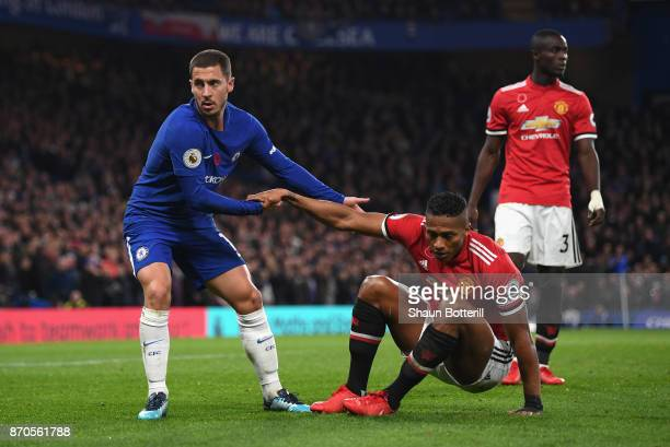 Eden Hazard of Chelsea helps up Antonio Valencia of Manchester United during the Premier League match between Chelsea and Manchester United at...