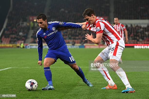 Eden Hazard of Chelsea holds off the challenge from Philipp Wollscheid of Stoke City during the Capital One Cup fourth round match between Stoke City...