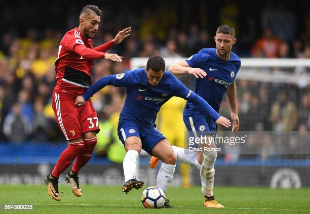 Eden Hazard of Chelsea is tackled by Roberto Pereyra of Watford as Gary Cahill of Chelsea looks on during the Premier League match between Chelsea...
