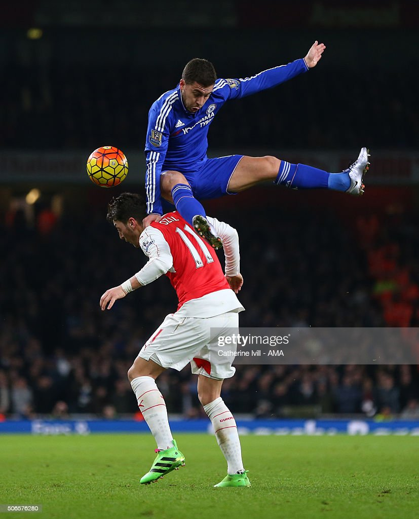 Eden Hazard of Chelsea jumps over Mesut Ozil of Arsenal during the Barclays Premier League match between Arsenal and Chelsea at the Emirates Stadium on January 24, 2016 in London, England.