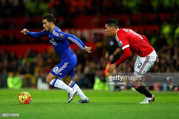 Eden Hazard of Chelsea runs with the ball under pressure from Chris Smalling of Manchester United during the Barclays Premier League match between...