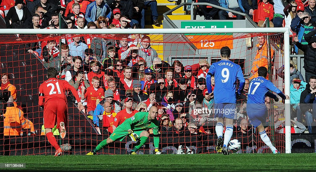 Eden Hazard (R) of Chelsea scores a penalty goal during the Barclays Premier League match between Liverpool and Chelsea at Anfield on April 21, 2013 in Liverpool, England.
