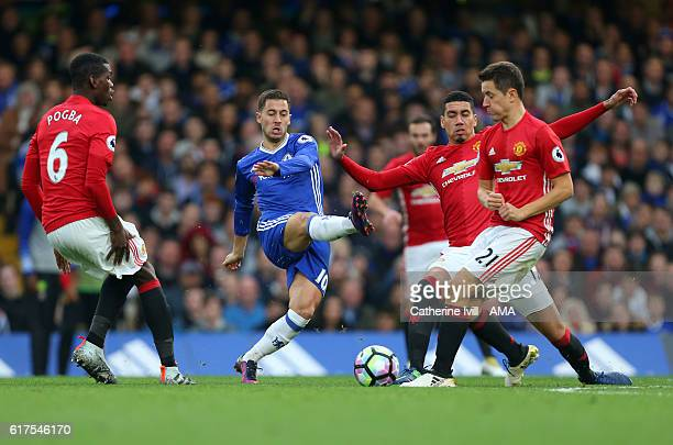 Eden Hazard of Chelsea tries to beat Paul Pogba Chris Smalling and Ander Herrera of Manchester United during the Premier League match between Chelsea...