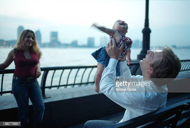 Eden Rose 7 months plays with her dad Dean Mills while mom Eve Mills left stands by as they sit in Battery Park along the Hudson River in New York...