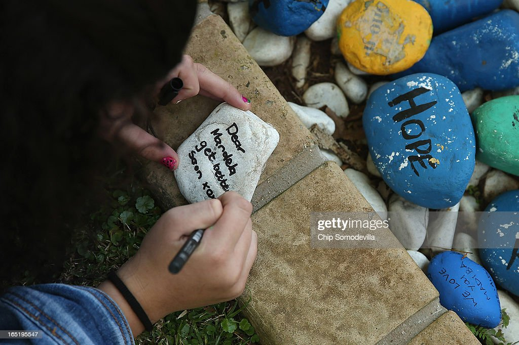 Eden Vogelman leaves a goodwill message written on a stone and placed inside a planter outside of former South Africa President Nelson Mandela's residence April 1, 2013 in Johannesburg, South Africa. Mandela, 94, is recovering from pneumonia in hospital, his third stay in the last four months. Referring to Mandela by clan name, Madiba, President Jacob Zuma said, 'We appeal to the people of South Africa and the world to pray for our beloved Madiba and his family and to keep them in their thoughts.' Mandela's lungs were damaged when he contracted tuberculosis during his 27 years in the infamous Robben Island prison. Mandela became the nation's first democratically elected president in 1994 following the end of apartheid.