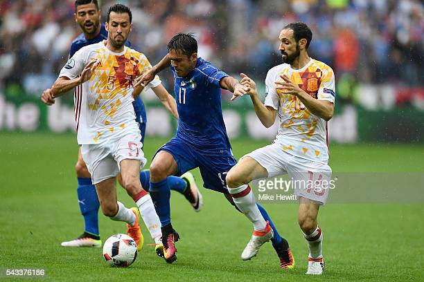 Eder of Italy is challenged by Sergio Busquets and Juanfran of Spain during the UEFA Euro 2016 Round of 16 match between Italy and Spain at Stade de...