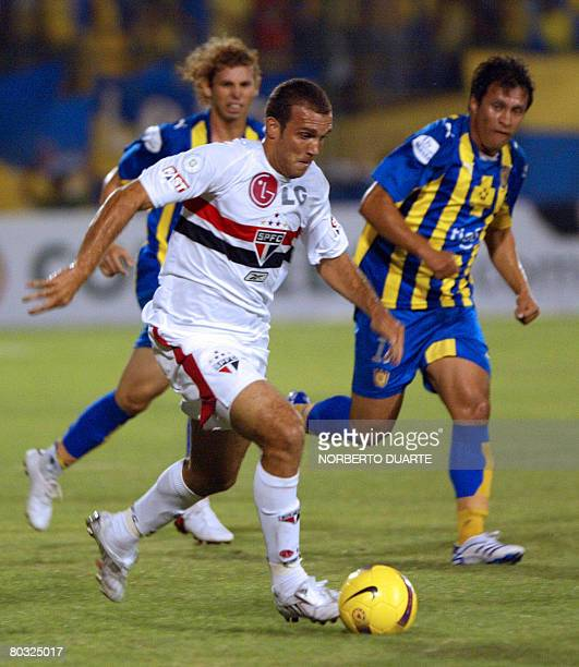 Eder Santana of Brazil's Sao Paulo drives the ball followed by Juan Angel Hermosilla of Paraguay's Sportivo Luqueo during a Libertadores Cup match on...