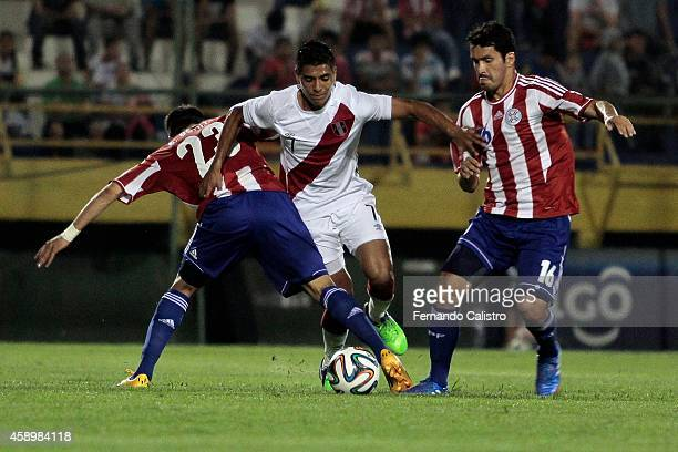 Edgar Benitez and Cristian Riveros Paraguay struggles for the ball with Paolo Hurtado of Peru during an international friendly match between Paraguay...
