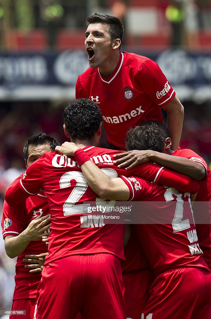 <a gi-track='captionPersonalityLinkClicked' href=/galleries/search?phrase=Edgar+Benitez&family=editorial&specificpeople=3433635 ng-click='$event.stopPropagation()'>Edgar Benitez</a> of Toluca celebrates woth his teammates after scoring the third goal against Xolos de Tijuana during the Quarterfinal second leg match between Toluca and Xolos de Tijuana as part of the Clausura 2014 Liga MX Playoffs at Nemesio Diez Stadium on May 04, 2014 in Toluca, Mexico.