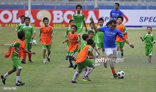 Edgar Davids former Dutch national team player plays football with Indonesian boys during a football clinic at Bung Karno stadium in Jakarta on...