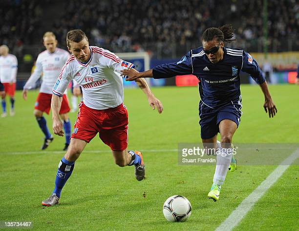 Edgar Davids of the friends team challenges for the ball with Michael Gravgaard of the HSV team during the charity Match Against Poverty between HSV...
