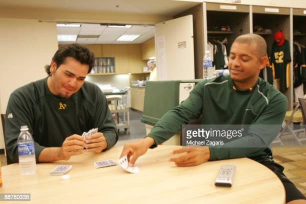 Edgar Gonzalez and Orlando Cabrera of the Oakland Athletics play cards in the clubhouse before the game against the Seattle Mariners at the Oakland...