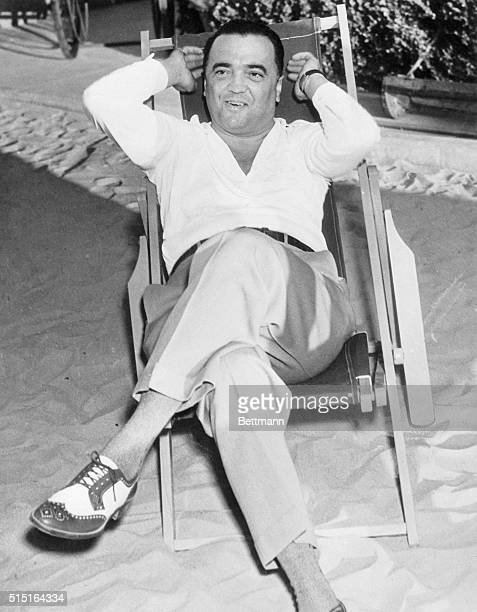 J Edgar Hoover Chief of the Federal Bureau of Investigation is shown taking in the sun at the Ambassador Hotel after his recent arrival here with...