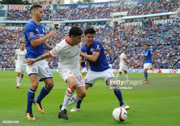 Edgar Mendez and Franciso Silva of Cruz Azul vie for the ball with Rubens Sambueza of Toluca during their Torneo Apertura 2017 football match at Azul...