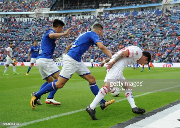 Edgar Mendez and Franciso Silva of Cruz Azul vies for the ball with Rubens Sambueza of Toluca during their Mexican Torneo Apertura 2017 football...