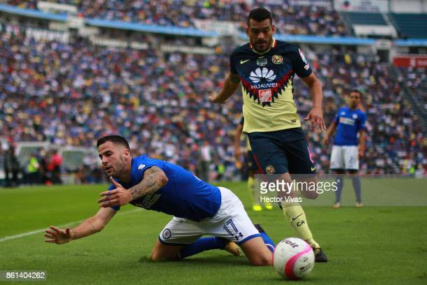 Edgar Mendez of Cruz Azul struggles for the ball with Miguel Angel Samudio of America during the 13th round match between Cruz Azul and America as...