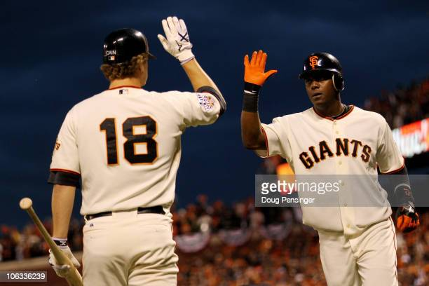 Edgar Renteria of the San Francisco Giants celebrates with Matt Cain after Renteria hits a fifth inning solo home run off of CJ Wilson of the Texas...