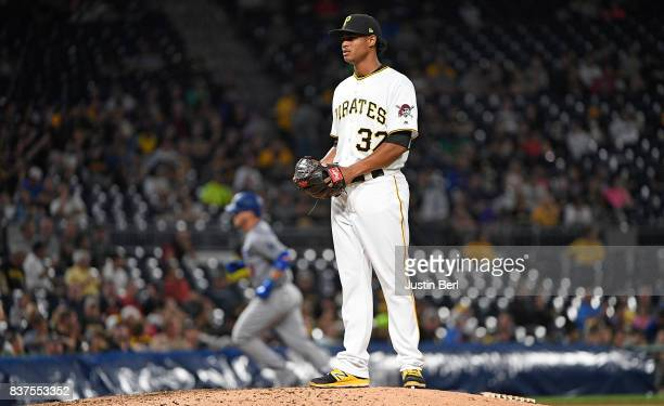 Edgar Santana of the Pittsburgh Pirates reacts as Yasmani Grandal of the Los Angeles Dodgers rounds the bases after hitting a two run home run in the...