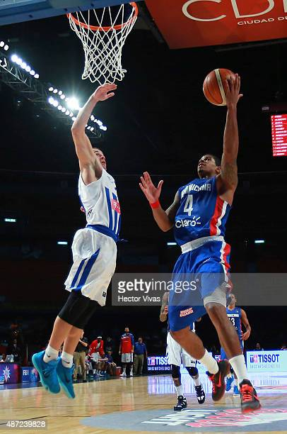 Edgar Sosa of Dominican Republic attempts to shoot the ball against Carlos Rivera of Puerto Rico during a second stage match between Puerto Rico and...