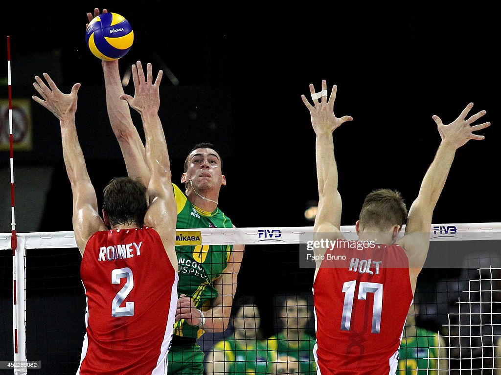 Edgar Thomas of Australia spikes the ball as Sean Rooney and Holt Maxwell of United States block during the FIVB World League Final Six match between United States and Australia at Mandela Forum on July 17, 2014 in Florence, Italy.