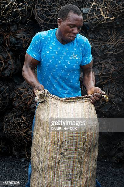 Edgar Zacharia lifts a sack of char powder gathered at a charcoal depot in Dar es Salaam on March 10 2015 ARTI Energy is a Tanzanian company...