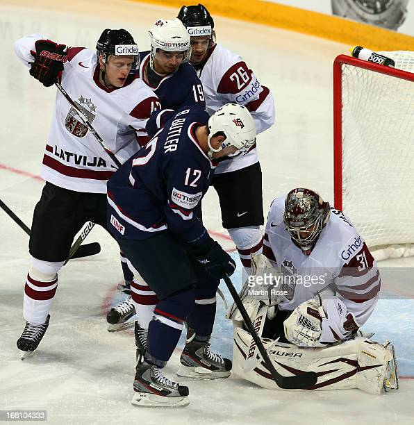 Edgars Masalskis goaltender of Latvia makes a save on Bobby Butler of USA battle during the IIHF World Championship group H match between Latvia and...