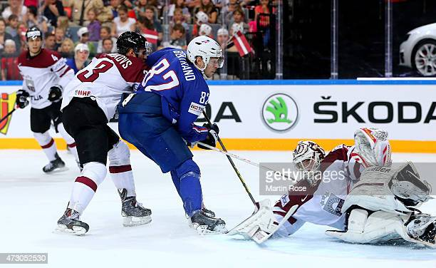 Edgars Masalskis goaltender of Latvia makes a save on Charles Bertrand of France battle for the puck during the IIHF World Championship group A match...