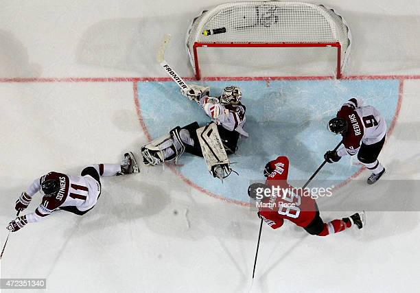 Edgars Masalskis goaltender of Latvia makes a save on Cody Almond of Switzerland during the IIHF World Championship group A match between Switzerland...