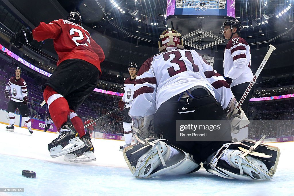 Edgars Masalskis #31 of Latvia gives up a goal in the second period to Martin Pluss #28 of Switzerland during the Men's Ice Hockey Qualification Playoff game on day eleven of the Sochi 2014 Winter Olympics at Bolshoy Ice Dome on February 18, 2014 in Sochi, Russia.