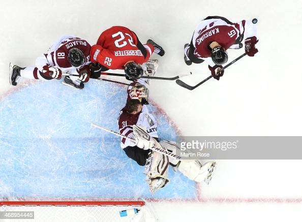 Edgars Masalskis of Latvia has his helmet knocked off while making a save against Nino Niederreiter of Switzerland as Georgijs Pujacs and Martins...