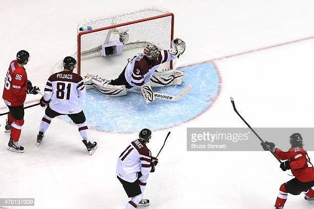 Edgars Masalskis of Latvia makes a glove save against Switzerland during the Men's Ice Hockey Qualification Playoff game on day eleven of the Sochi...