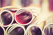 Close up edge of colorful magazine stacking roll with  blurry bookshelf background for publication and publishing concept , extremely DOF with vintage retro color tone