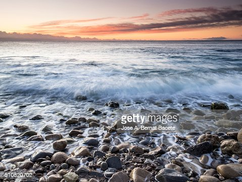 Edge of the sea in a coastal zone with waves and round rocks
