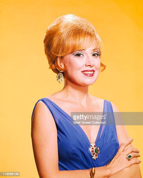 Edie Adams US singer actress and comedienne wearing a blue sleeveless top in a studio portrait against a yellow background circa 1960