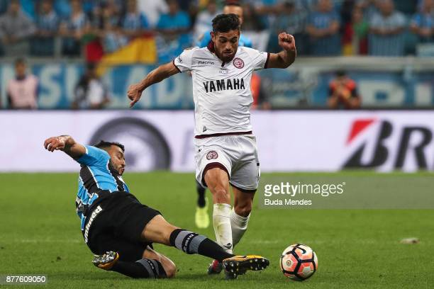 Edilson of Gremio struggles for the ball with Lautaro Costa of Lanus during a first leg match between Gremio and Lanus as part of Copa Bridgestone...