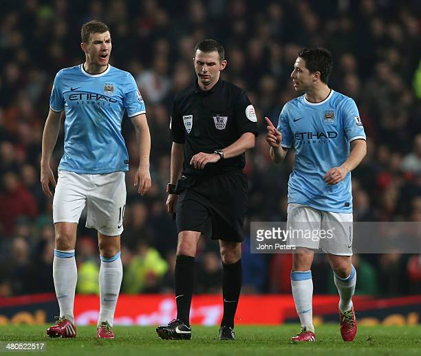Edin Dzeko and Samir Nasri of Manchester City complain to referee Michael Oliver during the Barclays Premier League match between Manchester United...