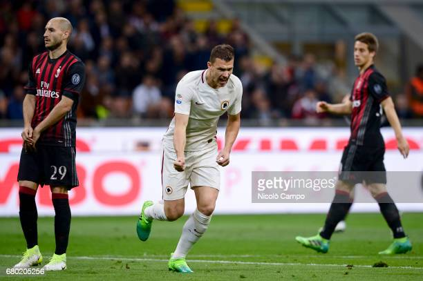 Edin Dzeko of AS Roma celebrates after scoring the opening goal while Gabriel Paletta and Mario Pasalic of AC Milan are disappointed during the Serie...