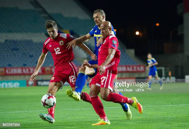 Edin Dzeko of Bosnia and Herzegovina tries to get between Jayce MascarenhasOlivero and Jason Pusey of Gibraltar during FIFA 2018 World Cup Qualifier...