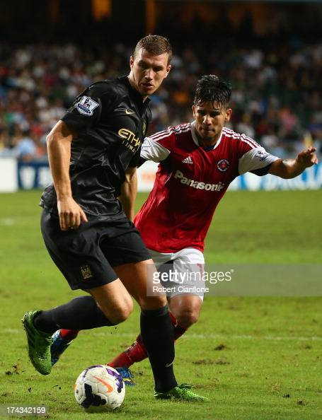 Edin Dzeko of Mancester City is pressured by his opponent during the Barclays Asia Trophy Semi Final match between Manchester City and South China at...