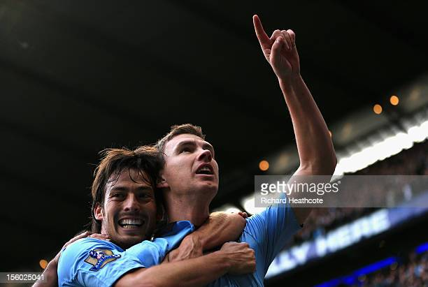 Edin Dzeko of Manchester City celebrates scoring his team's second goal with teammate David Silva during the Barclays Premier League match between...
