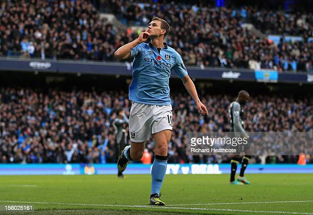 Edin Dzeko of Manchester City celebrates scoring his team's second goal during the Barclays Premier League match between Manchester City and...