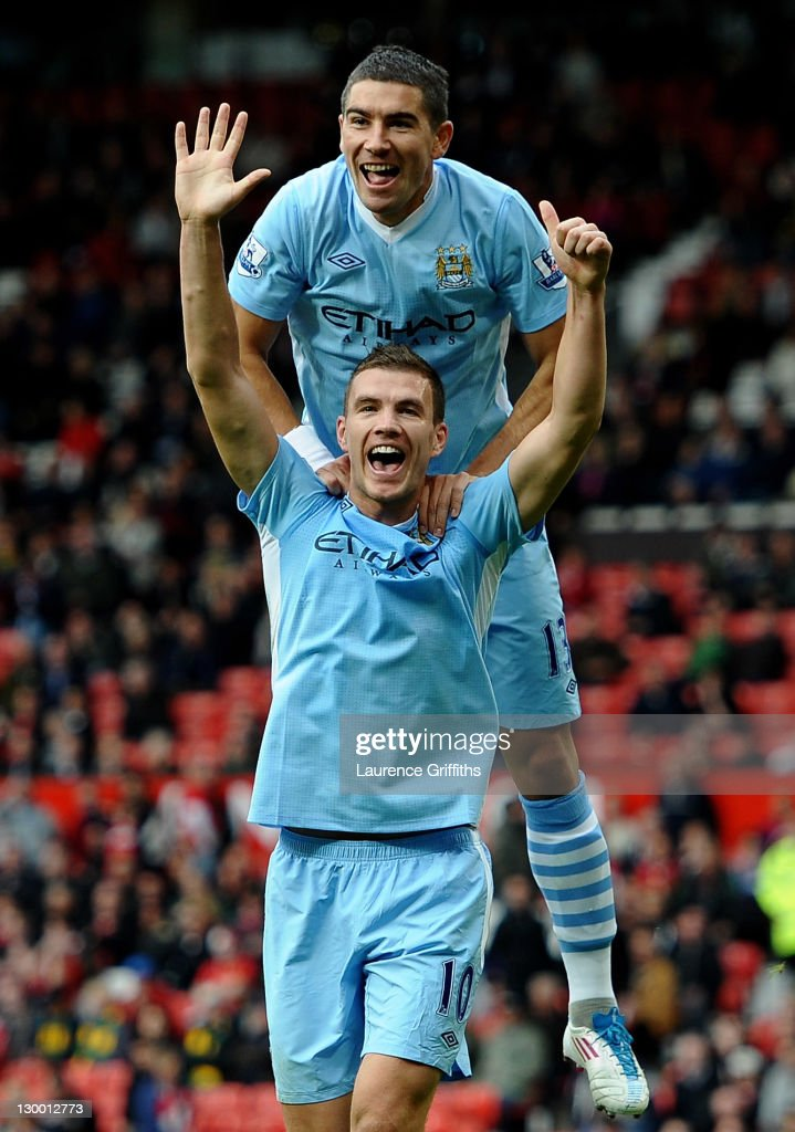 Edin Dzeko of Manchester City celebrates scoring his team's sixth goal with team mate Aleksandar Kolarov during the Barclays Premier League match between Manchester United and Manchester City at Old Trafford on October 23, 2011 in Manchester, England.