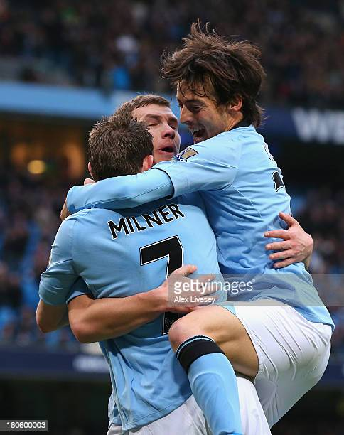 Edin Dzeko of Manchester City celebrates scoring the opening goal with teammates David Silva and James Milner during the Barclays Premier League...