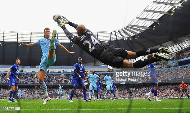 Edin Dzeko of Manchester City challenges as Tim Howard of Everton saves during the Barclays Premier League match between Manchester City and Everton...