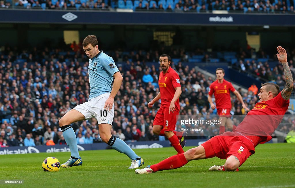 Edin Dzeko of Manchester City goes past the tackle of Daniel Agger of Liverpool to score the opening goal during the Barclays Premier League match between Manchester City and Liverpool at the Etihad Stadium on February 3, 2013 in Manchester, England.