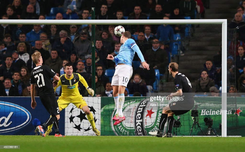 <a gi-track='captionPersonalityLinkClicked' href=/galleries/search?phrase=Edin+Dzeko&family=editorial&specificpeople=4404455 ng-click='$event.stopPropagation()'>Edin Dzeko</a> of Manchester City heads his team's fourth goal during the UEFA Champions League Group D match between Manchester City and FC Viktoria Plzen at Etihad Stadium on November 27, 2013 in Manchester, England.