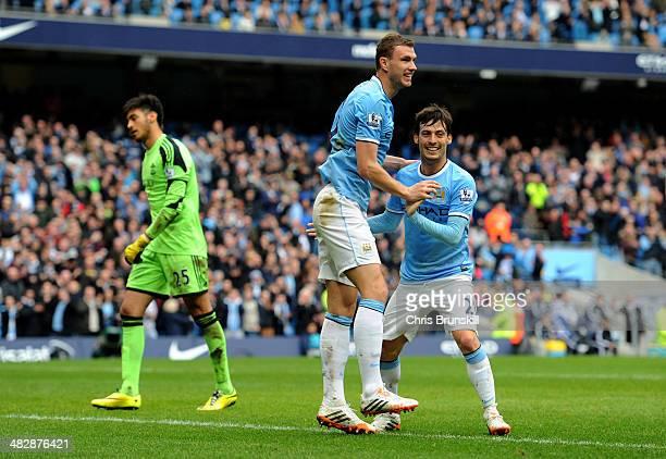 Edin Dzeko of Manchester City is congratulated by teammate David Silva after scoring his team's third goal as dejected goalkeeper Paulo Gazzaniga of...