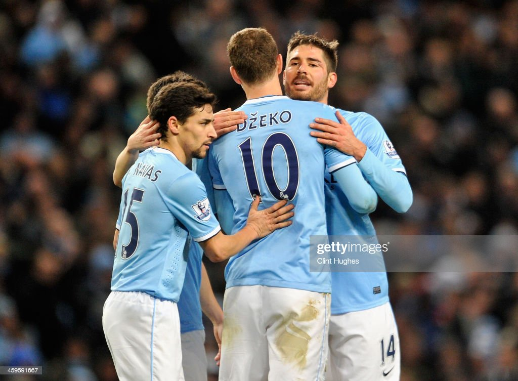 <a gi-track='captionPersonalityLinkClicked' href=/galleries/search?phrase=Edin+Dzeko&family=editorial&specificpeople=4404455 ng-click='$event.stopPropagation()'>Edin Dzeko</a> of Manchester City is congratulated by team-mates Javi Garcia (r) and Jesus Navas (l) during the Barclays Premier League match between Manchester City and Crystal Palace at the Etihad Stadium on December 28, 2013 in Manchester, England.