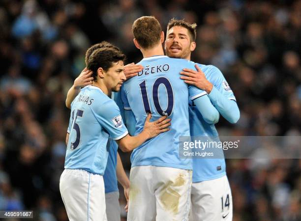 Edin Dzeko of Manchester City is congratulated by teammates Javi Garcia and Jesus Navas during the Barclays Premier League match between Manchester...